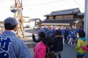積み上げられた松青葉の前で待機する刀抜き衆(村松町の御頭神事)