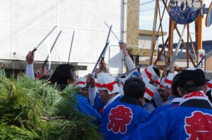 積み上げられた松青葉の前で刀を振り上げる刀抜き衆(村松町の御頭神事)