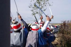 しめ縄の前で刀を振り上げる刀抜き衆(村松町の御頭神事)