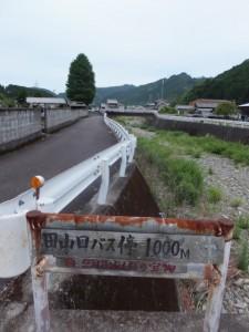 「田山口バス停1000m」の道標と墓地のケヤキ