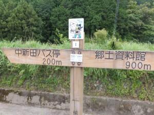 「中新田バス停 200m、郷土資料館 900m」の道標