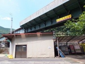JR紀勢本線と逢川が交差する付近の建物に「←熊野古道」の道標