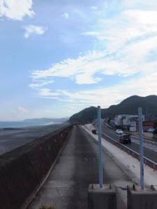 熊野市駅口交差点付近の防波堤上から望む七里御浜と国道42号