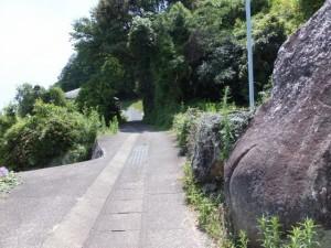 道の真ん中にある大石の海側を・・