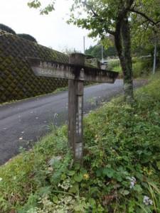 「←上多気バス停 0.2km、ホトトギスの水 0.9km・飼坂峠 1.4km (近畿自然歩道、伊勢本街道)」の道標